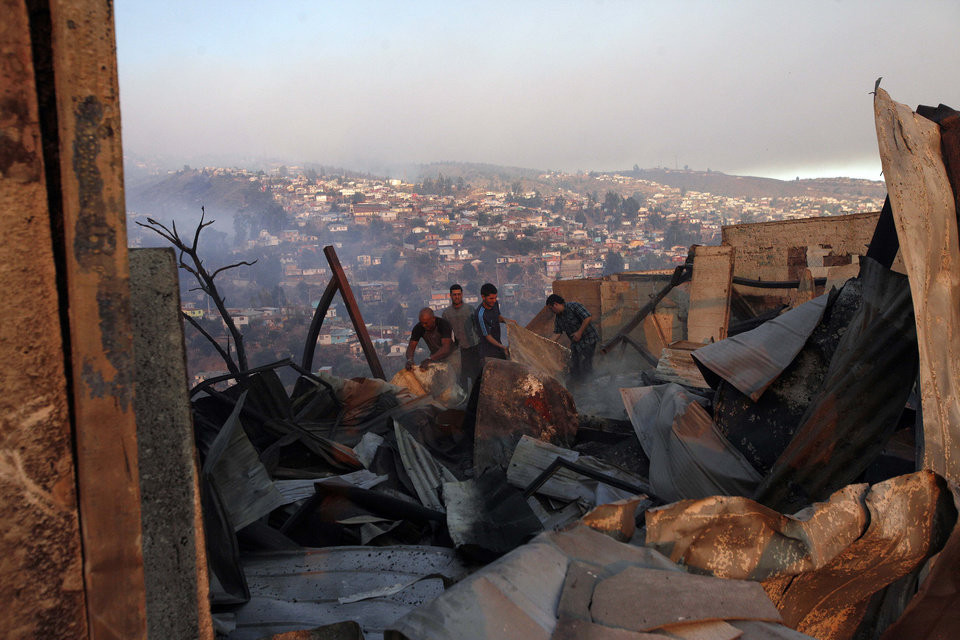 Photo - A group of people try to save items after a large forest fire reached urban areas in Valparaiso, Chile, Sunday April 13, 2014. Authorities say the fires have destroyed hundreds of homes, forced the evacuation of thousands and claimed the lives of at least seven people.  ( AP Photo/ Luis Hidalgo)