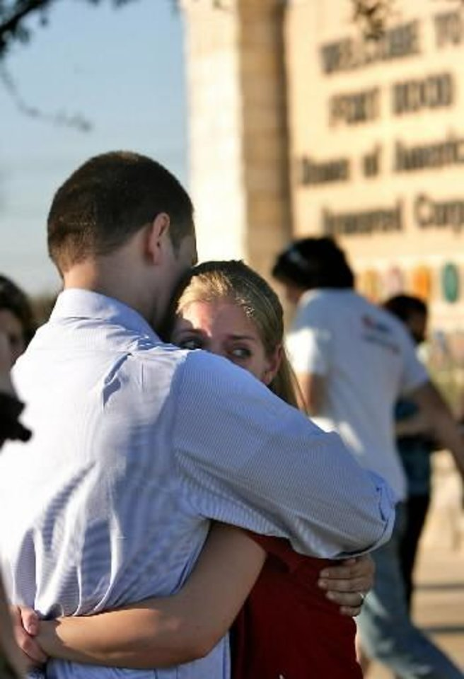Photo - Daniel Clark hugs and comforts his wife Rachel Clark outside of the main gate of  Fort  Hood near Killeen, Texas, Thursday, Nov. 5, 2009. Daniel's daughter, Madeline, 5, is in an elementary school on the post where it was locked down after a shooting happened on the base. (AP Photo/Austin American-Statesman, Rodolfo Gonzalez)