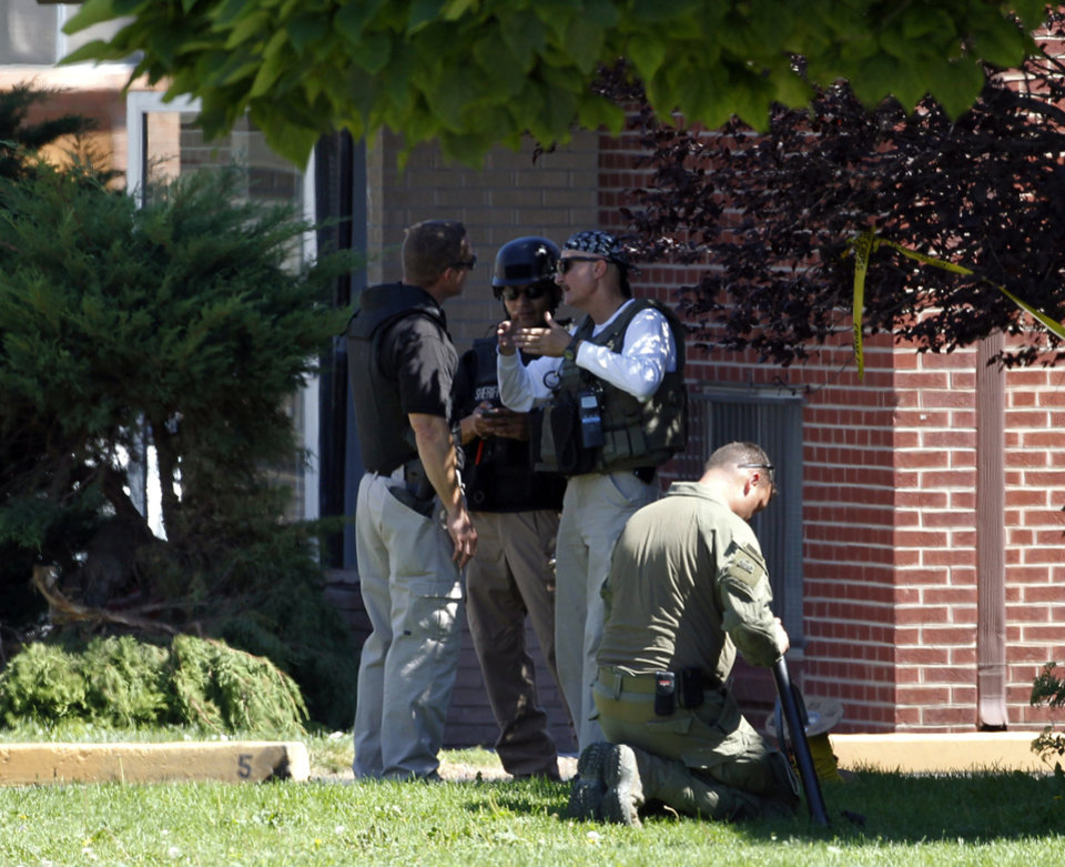 Photo -   Federal agents outside the apartment of James Holmes in Aurora, Colo., Saturday, July 21, 2012. Federal authorities detonated one small explosive and disarmed another inside Holmes' apartment, but several other explosive devices remained, said Aurora police Sgt. Cassidee Carlson. Twelve people were killed and dozens were injured in a shooting attack early Friday at a packed movie theater during a showing of the Batman movie,