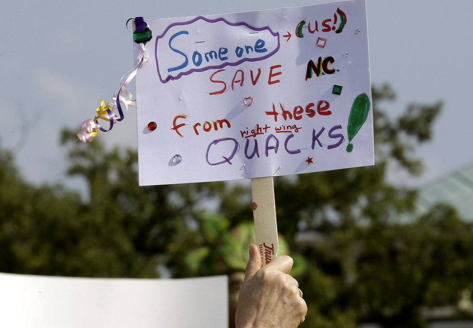 Photo - A protestor holds a sign as demonstrators gather at Halifax Mall near the state legislature in Raleigh, N.C., Monday, June 17, 2013. The National Association for the Advancement of Colored People and supporters of what the group calls