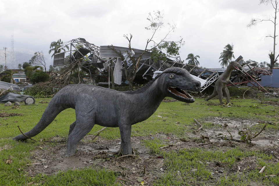 Sculptures of dinosaurs are left standing at a park which was damaged by the recent typhoon that hit New Bataan township, Compostela Valley in southern Philippines Sunday Dec. 9, 2012. The number of missing in the wake of the typhoon that devastated parts of the southern Philippines has jumped to nearly 900 after families and fishing companies reported losing contact with more than 300 fishermen in the South China Sea and Pacific Ocean, officials said Sunday.(AP Photo/Bullit Marquez)