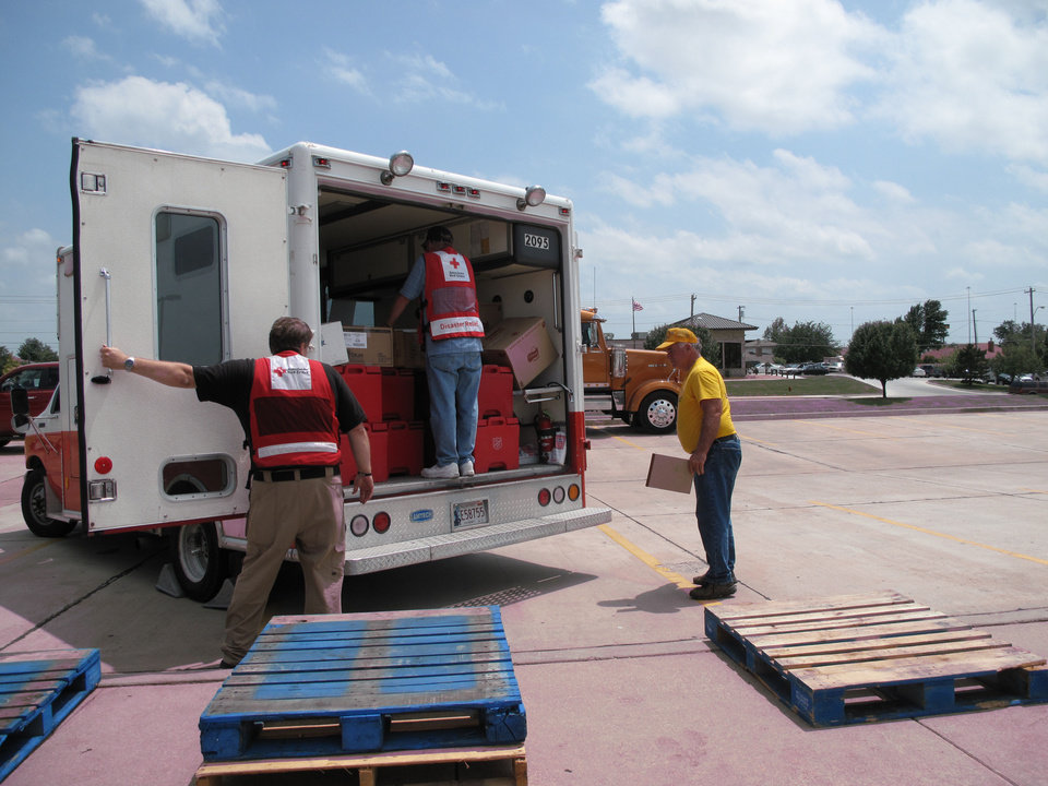 American Red Cross workers load meals onto a disaster relief truck as a Southern Baptist Disaster Relief volunteer looks on in the parking lot of First Baptist Church of Moore, 301 NE 27 in Moore. Southern Baptist Disaster Relief teams prepare the meals that are being distributed to tornado victims by the American Red Cross and Salvation Army. Photo by Carla Hinton <strong>Carla Hinton - The Oklahoman</strong>