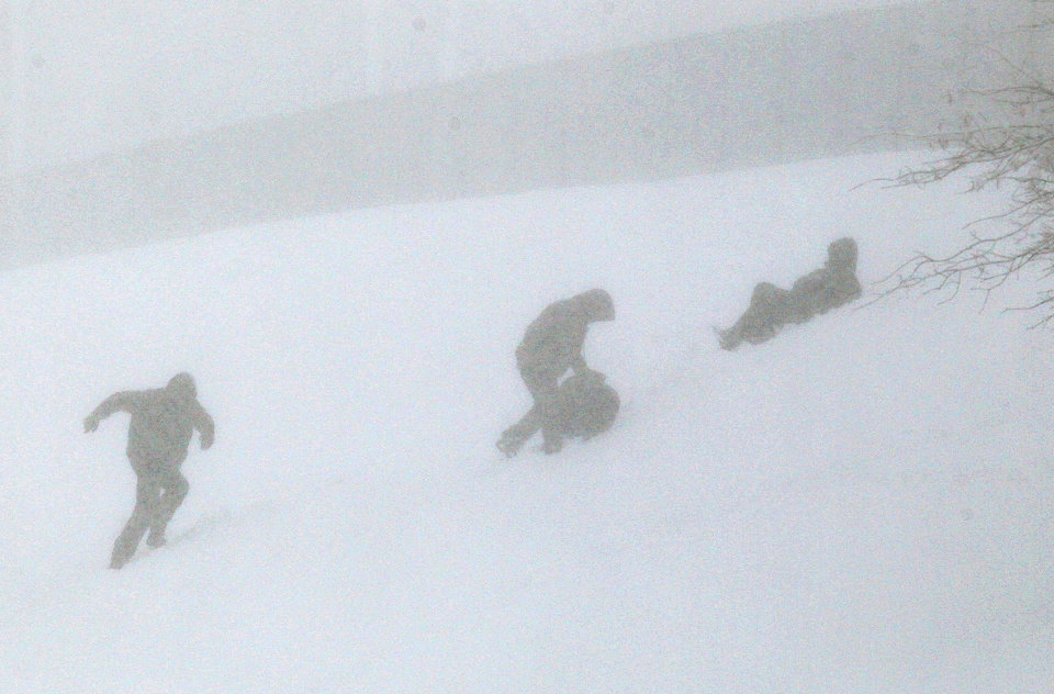 Children sled down and climb back up a hill on Klem Avenue in Overland, Mo., near St. Louis in nearly zero visibility as a Spring snowfall blankets the region on  Sunday, March 24, 2013. (AP Photo/St. Louis Post-Dispatch, Christian Gooden)
