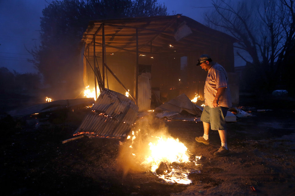 Photo - Phillip Green tries to put out hot spots near his burned storage building next to his home in Luther, Okla., after wildfire moved through the area on Friday, August 3, 2012. Photo by Bryan Terry, The Oklahoman