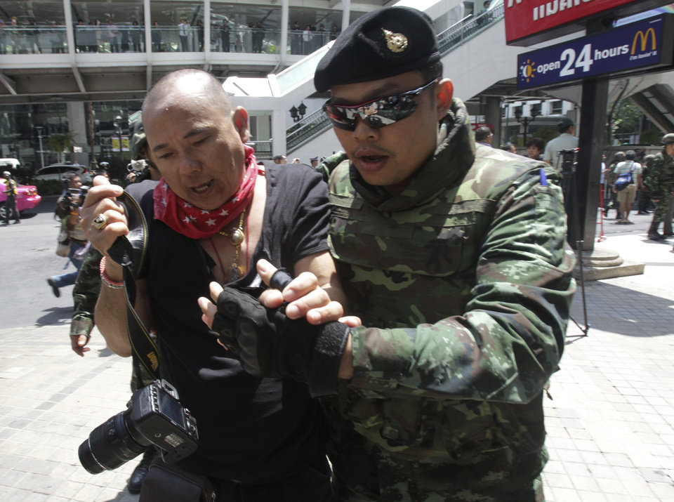 Photo - A protester, left, is detained by a Thai soldier during an anti-coup demonstration in Bangkok, Thailand, Sunday, May 25, 2014. The top general in Thailand's ruling junta warned people Sunday not to join anti-coup street protests, saying normal democratic principles cannot be applied at the time, as troops fanned out in central Bangkok to prevent rallies.(AP Photo/Sakchai Lalit)