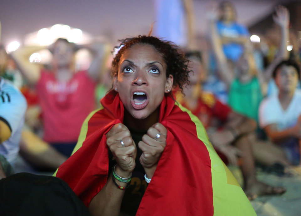 Photo - Wrapped in a Spanish national flag, a soccer fan reacts in frustration as she watches the live broadcast of the World Cup match between Spain and the Netherlands inside the FIFA Fan Fest area on Copacabana beach in Rio de Janeiro, Brazil, Friday, June 13, 2014. The Netherlands thrashed Spain 5-1 Friday. It was a humiliating defeat for the defending World Cup champions. (AP Photo/Leo Correa)
