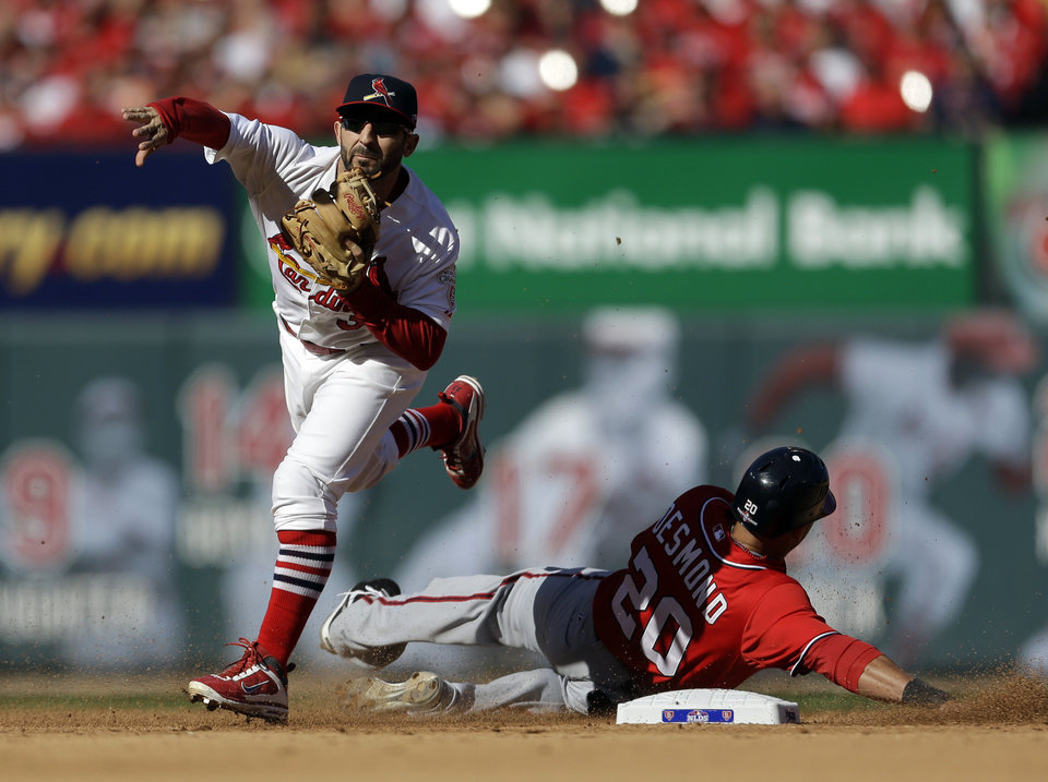 Washington Nationals' Ian Desmond, right, is out at second as St. Louis Cardinals second baseman Daniel Descalso fails to turn the double play during the fourth inning in Game 1 of baseball's National League division series Sunday, Oct. 7, 2012, in St. Louis. The Nationals' Kurt Suzuki was safe at first. (AP Photo/Jeff Roberson)