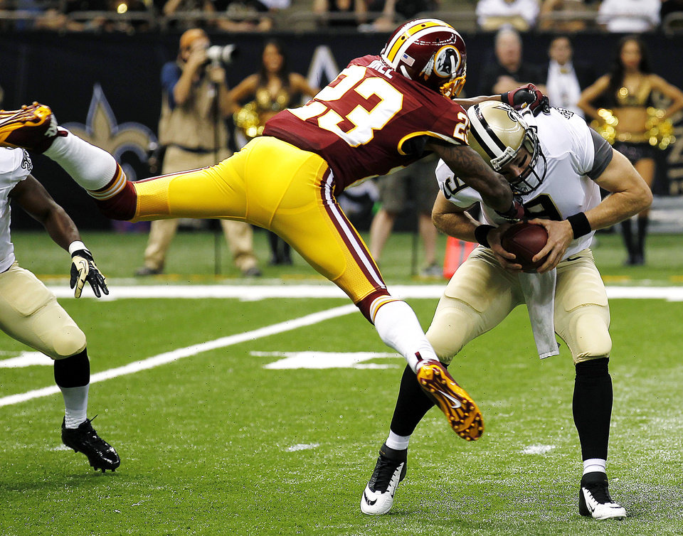 Photo -   New Orleans Saints quarterback Drew Brees (9) is sacked by Washington Redskins cornerback DeAngelo Hall (23) in the first half of an NFL football game in New Orleans, Sunday, Sept. 9, 2012. The Redskins won 40-32. (AP Photo/Bill Haber)