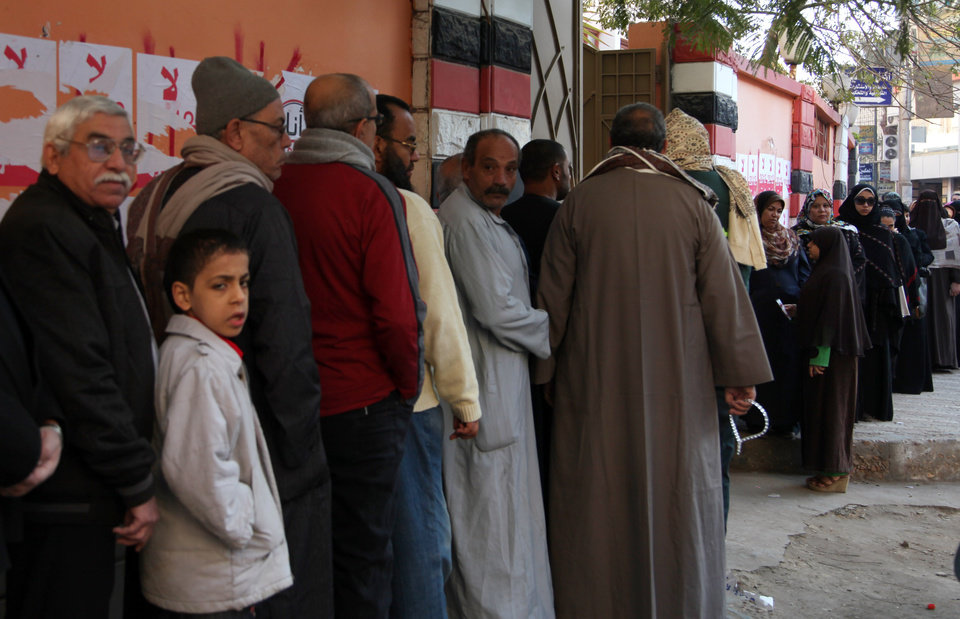 Photo - Egyptians line up outside a polling station as they wait their turn to cast their votes in the second round of a referendum on a disputed constitution drafted by Islamist supporters of President Mohammed Morsi  in Fayoum, about 100 kilometers ( 62 miles ) south of Cairo, Egypt, Saturday, Dec. 22, 2012.(AP Photo/Khalil Hamra)