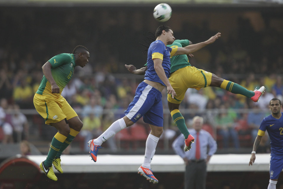 Photo -   South Africa's Dkigacoi, left, and his teammate Tshabalala, right, fight to head the ball against Brazil's Leandro Damiao during a friendly soccer match in Sao Paulo, Brazil, Friday, Sept. 7, 2012. (AP Photo/Nelson Antoine)