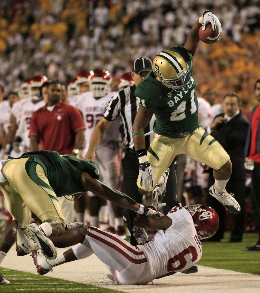 Baylor running back Jarred Salubi (21) leaps out of bounds over Oklahoma' Demontre Hurst (6) following a long run in the first half of an NCAA college football game Saturday, Nov. 19, 2011, in Waco, Texas. (AP Photo/Tony Gutierrez)