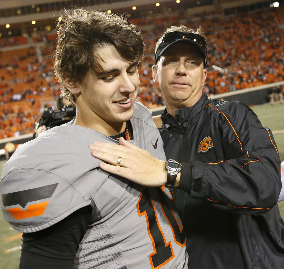 Photo - Oklahoma State offensive coordinator Todd Monken, right, embraces quarterback Clint Chelf (17) after a college football game between Oklahoma State University (OSU) and West Virginia University (WVU) at Boone Pickens Stadium in Stillwater, Okla., Saturday, Nov. 10, 2012. OSU won, 55-34. Photo by Nate Billings, The Oklahoman