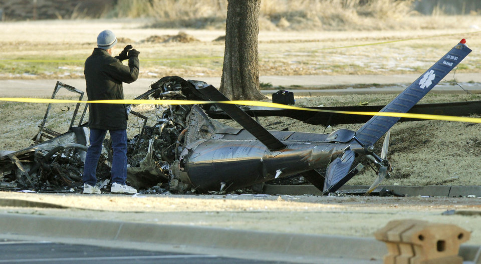 Investigators with the FAA look over the wreckage of a medical helicopter which crashed in front of the Saint Ann Retirement Center on Britton Road between Rockwell and Council Roads in Oklahoma City, OK, Friday, February 22, 2013. Two people were killed in the crash.  By Paul Hellstern, The Oklahoman