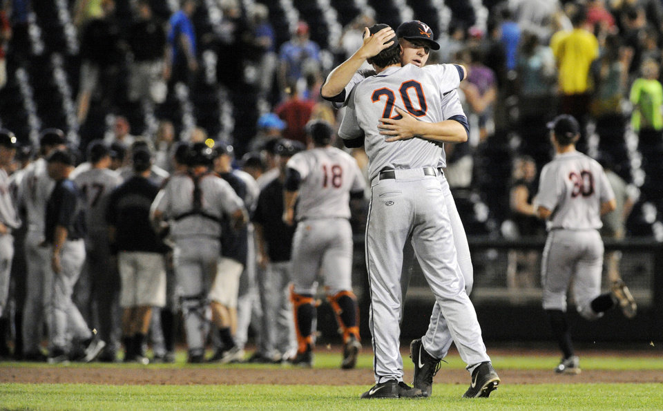 Photo - Virginia pitcher Brandon Waddell (20) celebrates with Artie Lewicki after Virginia defeated Vanderbilt 7-2 in Game 2 of the best-of-three NCAA baseball College World Series finals in Omaha, Neb., Tuesday, June 24, 2014. (AP Photo/Eric Francis)