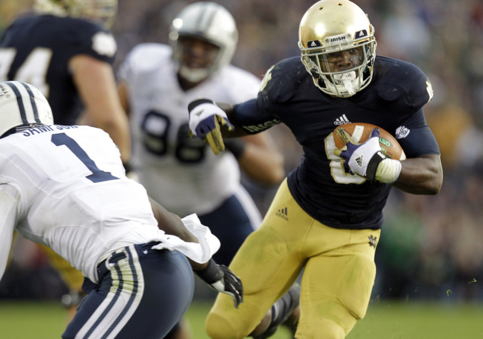 Photo -   Notre Dame running back Theo Riddick, right, runs past BYU defensive back Joe Sampson during the second half of an NCAA college football game in South Bend, Ind., Saturday, Oct. 20, 2012. Notre Dame defeated BYU 17-14. (AP Photo/Michael Conroy)