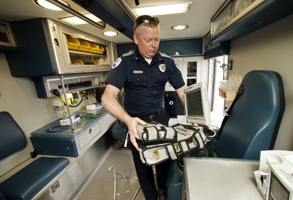 Photo - EMSSTAT paramedic Kevin Ring loads brings equipment into one of the service's largest ambulances. PHOTO BY STEVE SISNEY, THE OKLAHOMAN  STEVE SISNEY