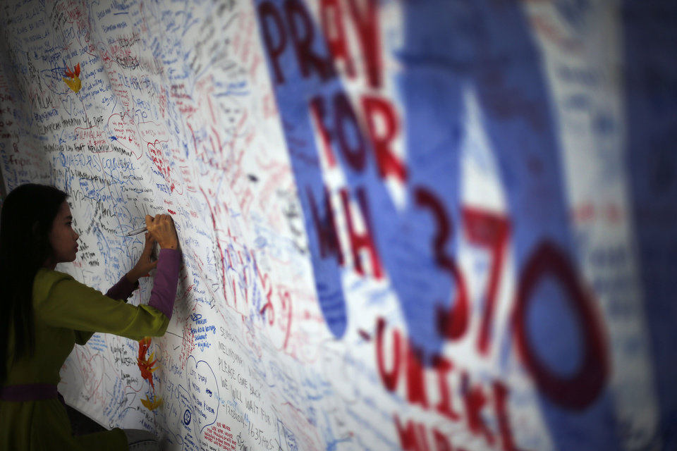 Photo - A woman writes on a board of messages and well-wishes dedicated to people involved with the missing Malaysia Airlines jetliner MH370, Saturday, March 15, 2014 in Sepang, Malaysia. The Malaysian passenger jet missing for more than a week had its communications deliberately disabled and its last signal came about seven and a half hours after takeoff, meaning it could have ended up as far as Kazakhstan or deep in the southern Indian Ocean, Malaysia's Prime Minister Najib Razak said Saturday. (AP Photo/Wong Maye-E)