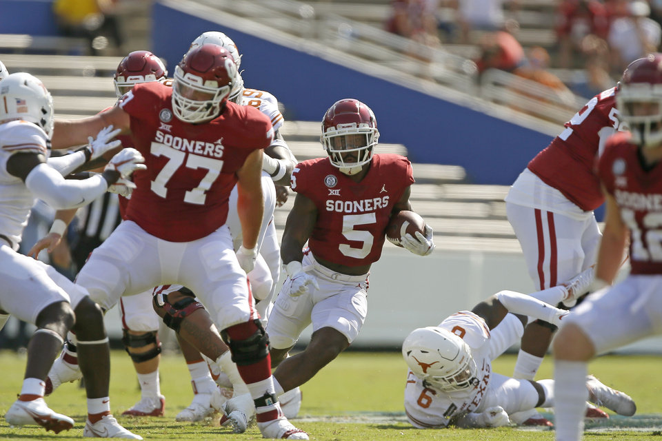 Photo - Oklahoma's T.J. Pledger (5) carries the ball during the Red River Showdown college football game between the University of Oklahoma Sooners (OU) and the Texas Longhorns (UT) at Cotton Bowl Stadium in Dallas, Saturday, Oct. 10, 2020. Oklahoma won 53-45 in four overtimes. [Bryan Terry/The Oklahoman]