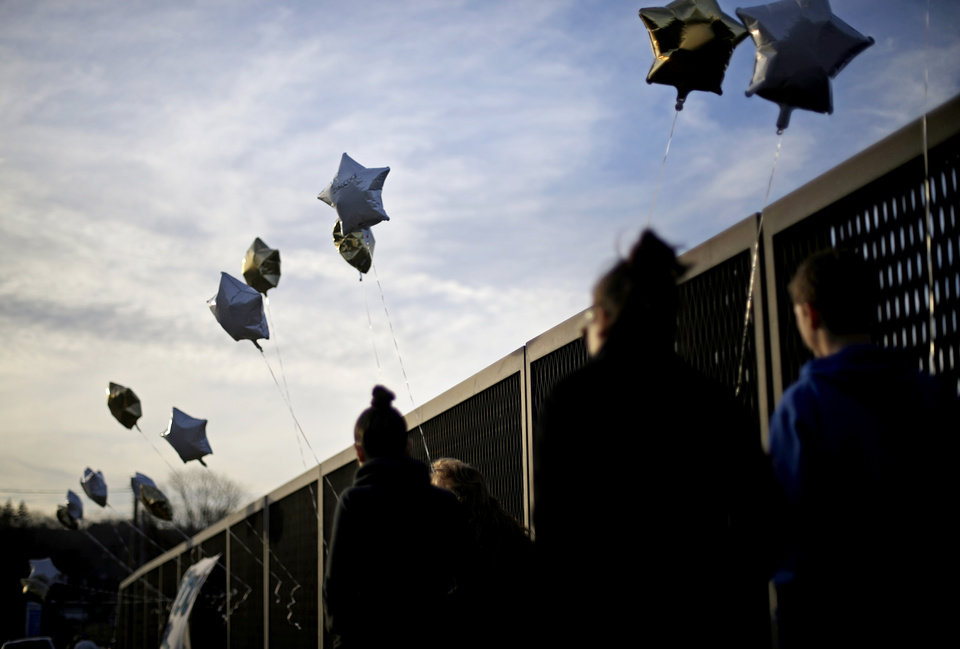 Photo - Balloons tied by nearby residents decorate an overpass up the road from the Sandy Hook Elementary School, Saturday, Dec. 15, 2012, in Newtown, Conn. The massacre of 26 children and adults at Sandy Hook Elementary school elicited horror and soul-searching around the world even as it raised more basic questions about why the gunman, 20-year-old Adam Lanza, would have been driven to such a crime and how he chose his victims. (AP Photo/David Goldman) ORG XMIT: CTDG123