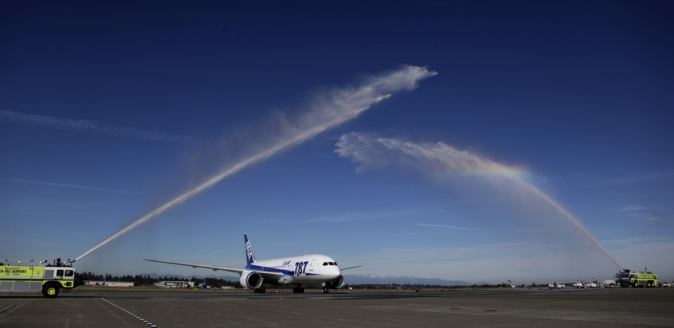 A Boeing 787 operated by All Nippon Airways taxis under water streams from fire trucks at Seattle-Tacoma International Airport, Monday, Oct. 1, 2012, during an official welcome ceremony after it landed on the first day of service for the 787 on ANA's Seattle-Tokyo route. (AP Photo/Ted S. Warren)