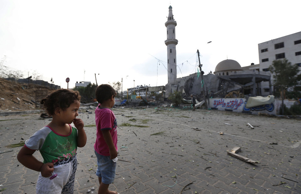 Photo - Palestinian children inspect the damage at the Al Aqsa Martyrs mosque in Gaza City, destroyed by an overnight Israeli strike, Tuesday, July 22, 2014. A high-level attempt by the U.N. chief and the U.S. secretary of state to end deadly Israel-Hamas fighting was off to a rough start Monday: Gaza's Hamas rulers signaled they won't agree to an unconditional cease-fire, Israel's prime minister said he'll do whatever is necessary to keep Israelis safe from Hamas attacks. Gaza health officials say hundreds Palestinians have died since the beginning of Israel's campaign in the Gaza Strip since the ground operation began Thursday. (AP Photo/Lefteris Pitarakis)