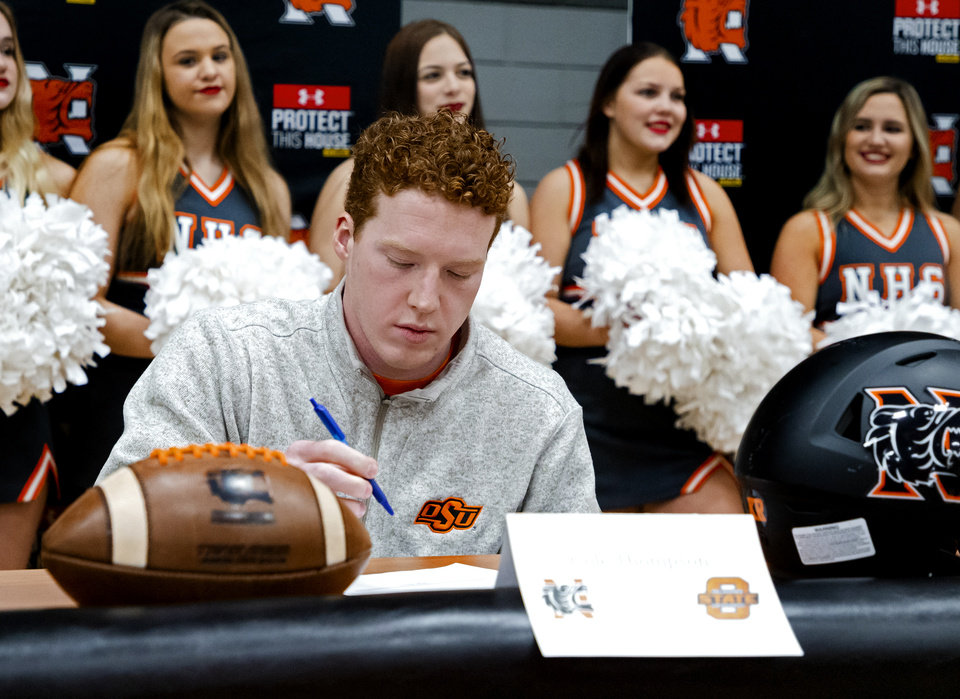 Photo - Oklahoma State University signee Cole Thompson celebrates signing his letter of intent during a national signing day ceremony for football at Norman High School in Norman Okla. on Wednesday, Dec. 18, 2019.   [Chris Landsberger/The Oklahoman]