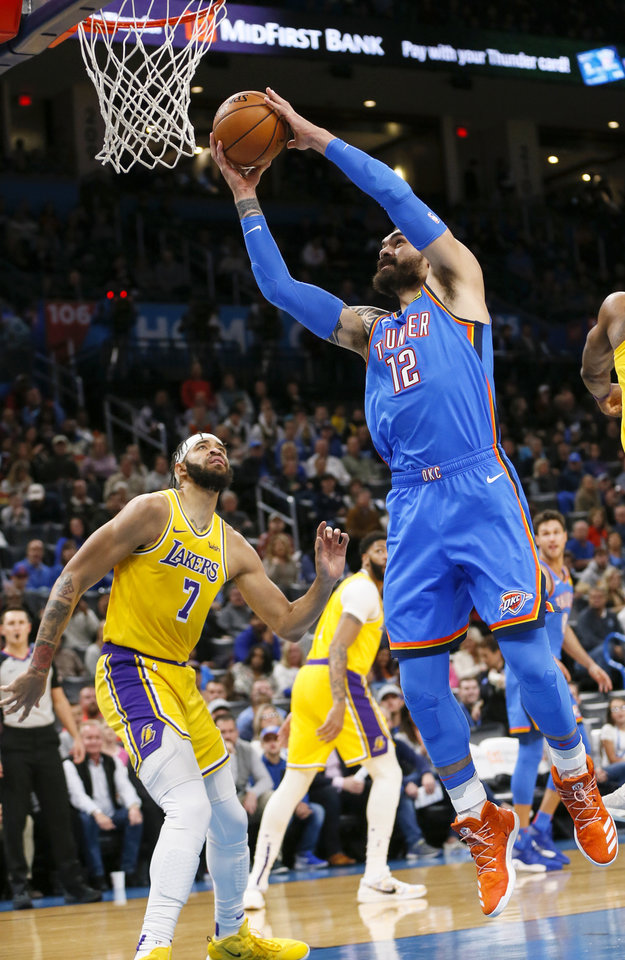 Photo - Oklahoma City's Steven Adams (12) takes the ball to the hoop next to Los Angeles' JaVale McGee (7) in the first quarter during an NBA basketball game between the Oklahoma City Thunder and the Los Angeles Lakers at Chesapeake Energy Arena in Oklahoma City, Friday, Nov. 22, 2019. [Nate Billings/The Oklahoman]
