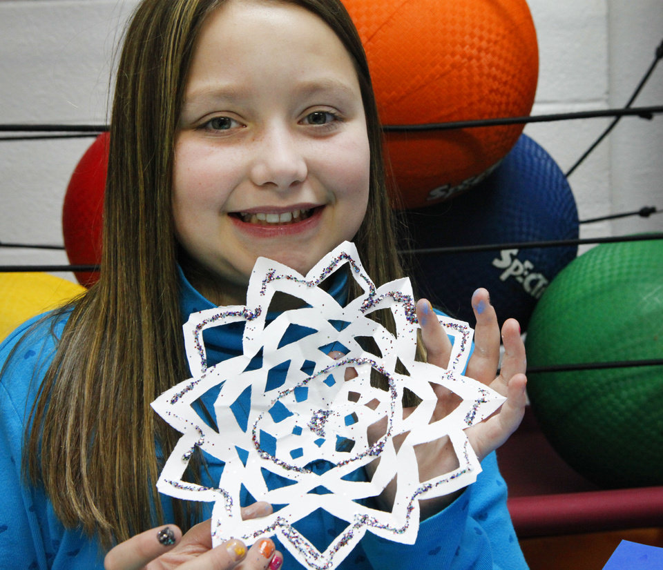Photo - Faith Money, 10, holds the snowflake she made to send to the students at Sandy Hook Elementary.