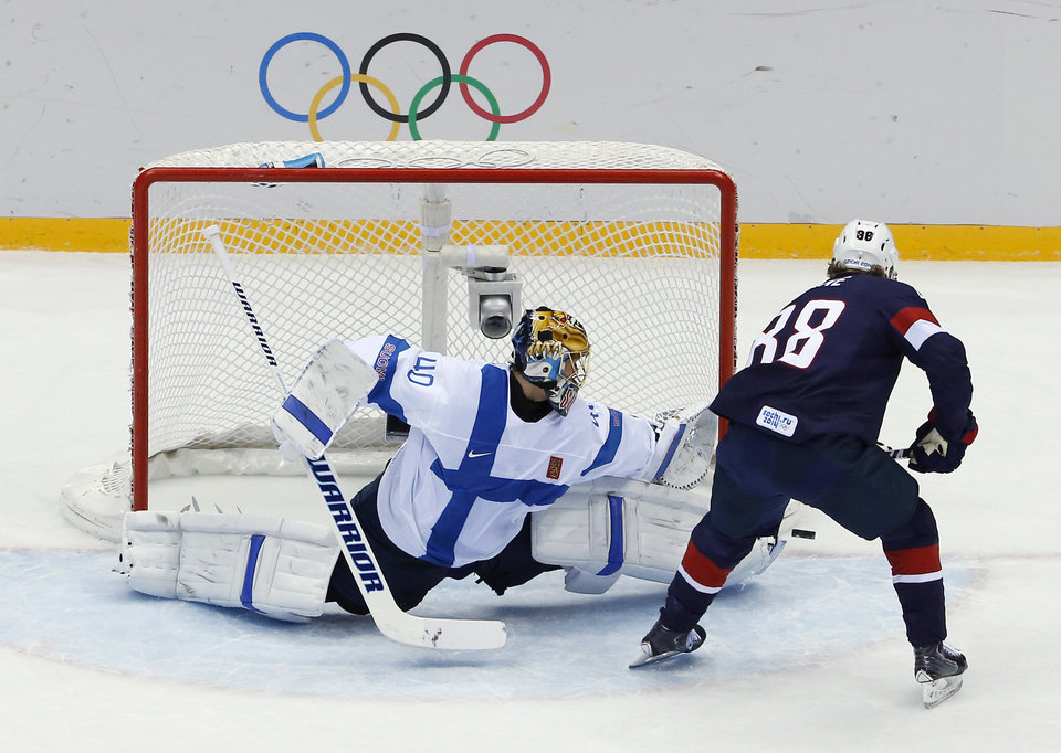 Photo - Finland goaltender Tuukka Rask blocks a shot by USA forward Patrick Kane during the first period of the men's bronze medal ice hockey game at the 2014 Winter Olympics, Saturday, Feb. 22, 2014, in Sochi, Russia. (AP Photo/David J. Phillip )