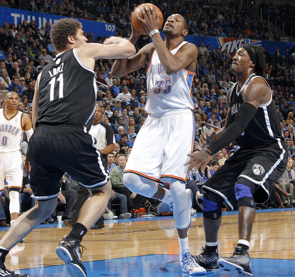 Photo - Oklahoma City's Kevin Durant (35) drives to the basket past Brooklyn Nets' Brook Lopez (11) and Gerald Wallace (45) during the NBA basketball game between the Oklahoma City Thunder and the Brooklyn Nets at the Chesapeake Energy Arena on Wednesday, Jan. 2, 2013, in Oklahoma City, Okla. Photo by Chris Landsberger, The Oklahoman
