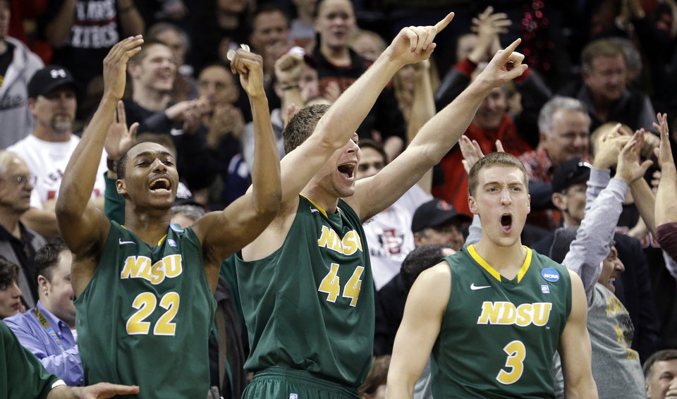 Photo - Players on the North Dakota State bench stand and cheer as their team takes the lead against Oklahoma in overtime during a second-round game of the NCAA men's college basketball tournament in Spokane, Wash., Thursday, March 20, 2014. North Dakota State won 80-75 in overtime. (AP Photo/Elaine Thompson)