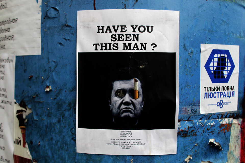 Photo - A poster with a photo of fugitive Ukrainian President Viktor Yanukovych, who fled the capital Kiev and went into hiding after months of protests against his government, is seen fixed onto a barricade in central Kiev, Ukraine, Thursday, Feb. 27, 2014. Ukraine put its police on high alert after dozens of armed pro-Russia men stormed and seized local government buildings in Ukraine's Crimea region early Thursday and raised a Russian flag over a barricade. (AP Photo/Marko Drobnjakovic)