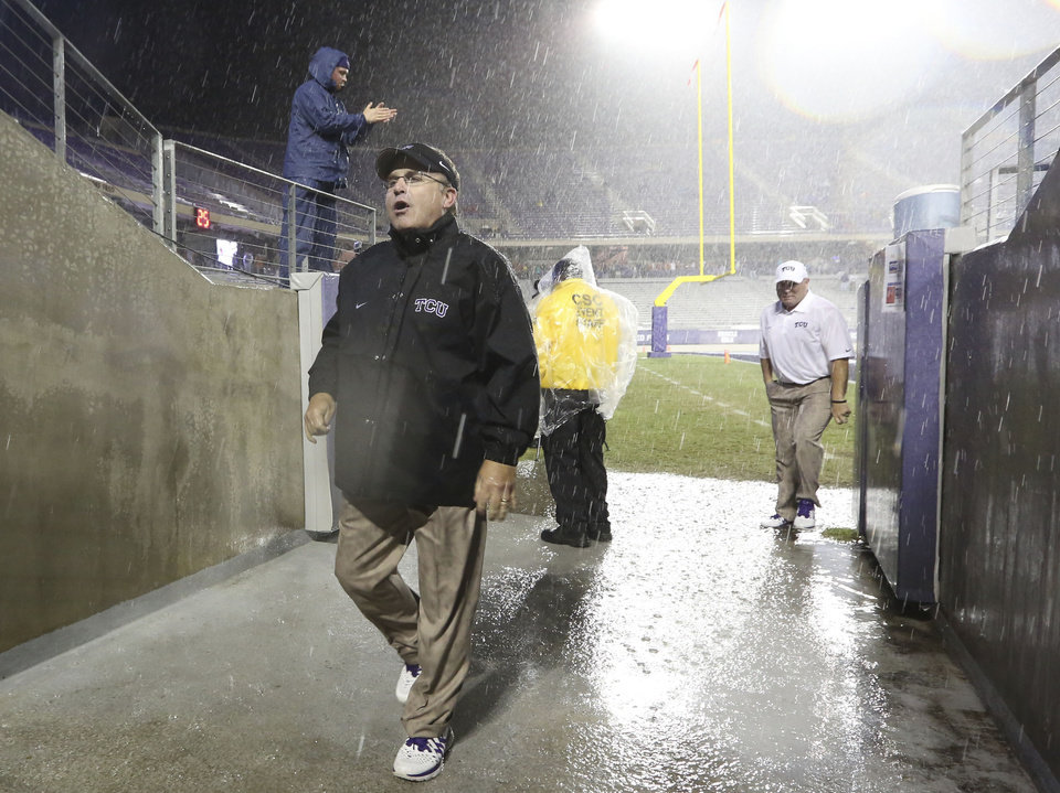 Photo - TCU head coach Gary Patterson walks into the visitor's tunnel on his way to meet with Texas coach Mack Brown during a thunder delay during the second quarter of an NCAA college football game on Saturday, Oct. 26, 2013, in Fort Worth, Texas. The teams agreed to play the remainder of the second quarter after half-time with a five-minute break between the second and third quarters.  (AP Photo/LM Otero)