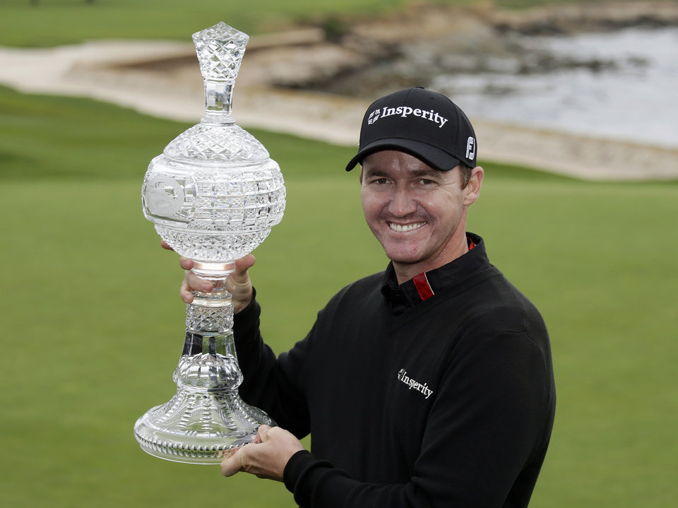 Photo - Jimmy Walker poses with his trophy on the 18th green of the Pebble Beach Golf Links after winning the AT&T Pebble Beach Pro-Am golf tournament Sunday, Feb. 9, 2014, in Pebble Beach, Calif. Walker shot a 2-over-par 74 to finish at total 11-under-par. (AP Photo/Eric Risberg)