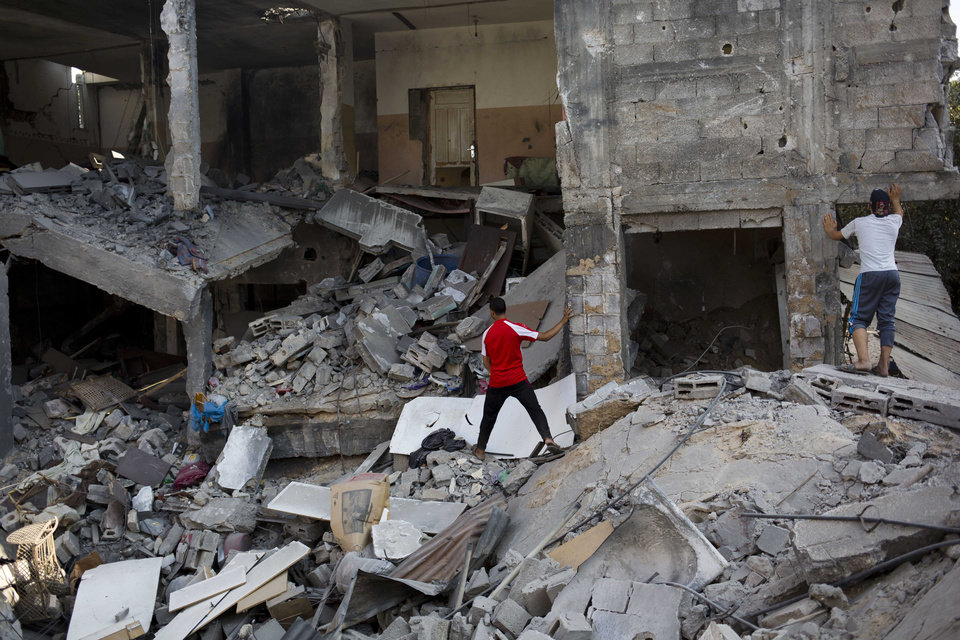 Photo - Palestinians inspect a destroyed house in the heavily bombed Gaza City neighborhood of Shijaiyah, close to the Israeli border, Friday, Aug. 1, 2014. A three-day Gaza cease-fire that began Friday quickly unraveled, with Israel and Hamas accusing each other of violating the truce. (AP Photo/Dusan Vranic)