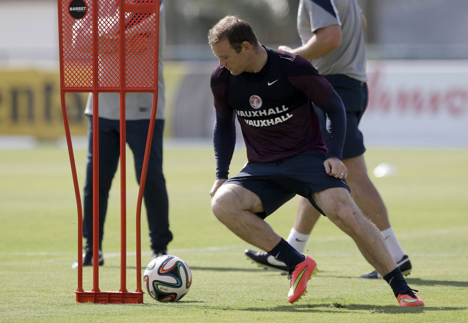 Photo - England national soccer team player Wayne Rooney takes part in a squad training session for the 2014 soccer World Cup at the Urca military base in Rio de Janeiro, Brazil, Monday, June 16, 2014.  (AP Photo/Matt Dunham)