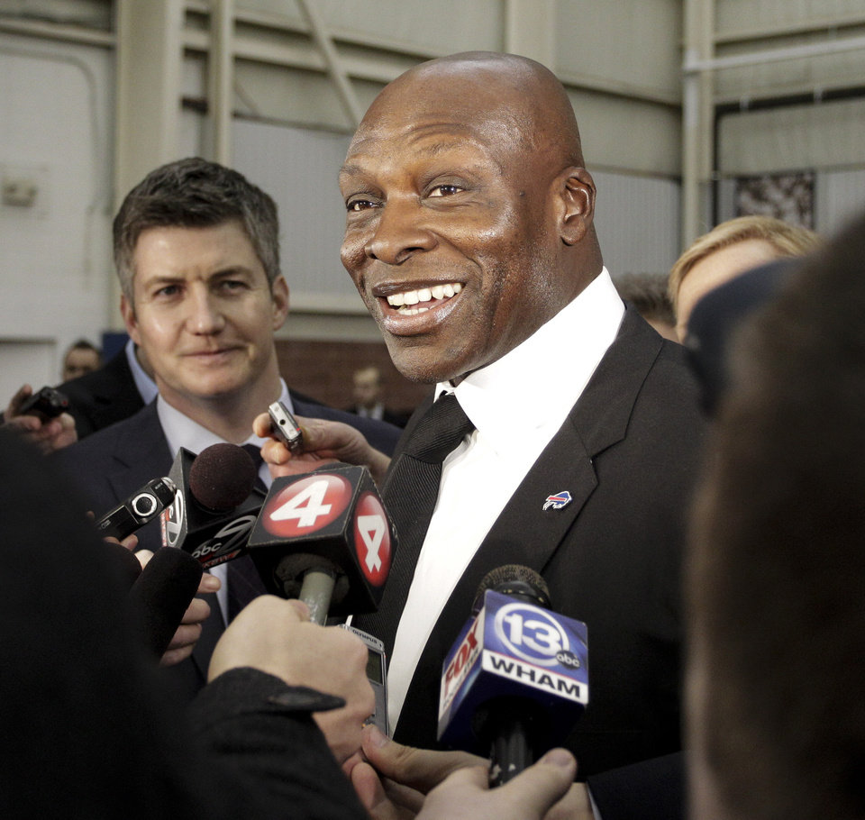 Photo - Buffalo Bills hall of fame defensive end Bruce Smith answers questions from the media during a public memorial and remembrance being held inside the NFL football team's fieldhouse for Buffalo Bills owner Ralph C. Wilson in Orchard Park, N.Y., Saturday, April 5, 2014. Wilson, the team's founder and sole owner, died March 25. (AP Photo/Nick LoVerde)