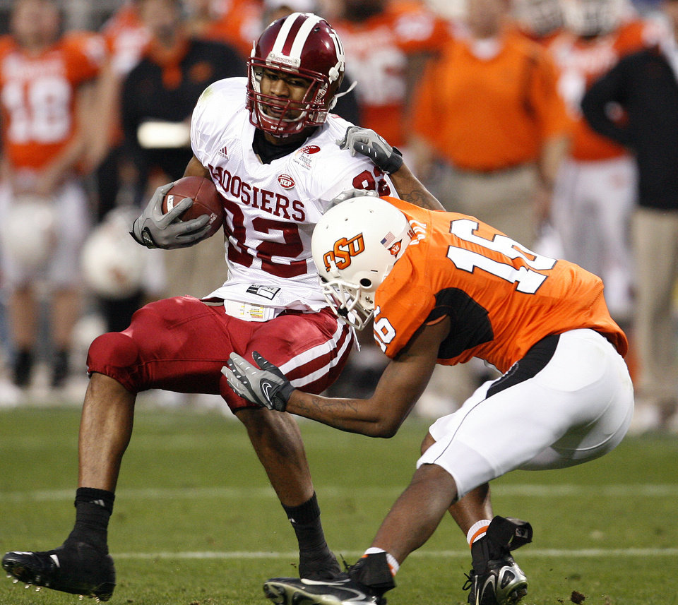 Photo - Oklahoma State's Perrish Cox (16) drags down Indiana's James Hardy (82) in the first half during the Insight Bowl college football game between Oklahoma State University (OSU) and the Indiana University Hoosiers (IU) at Sun Devil Stadium on Monday, Dec. 31, 2007, in Tempe, Ariz. 