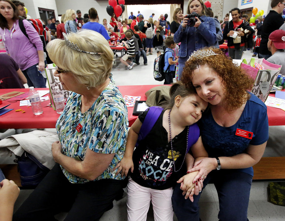 A pre-K student sits between her teachers, Linda Patterson, left, and Kaye Johnson after walking up to them and giving both a hug. There was lots of hugging and plenty of joy at Eastlake Elementary School on SW 134 when Eastlake School hosted a reunion of students, parents, teachers and families from Plaza Towers Elementary School. Seven students died at Plaza Towers School in Monday\'s EF-5 tornado, which also destroyed the school. Photo by Jim Beckel, The Oklahoman.