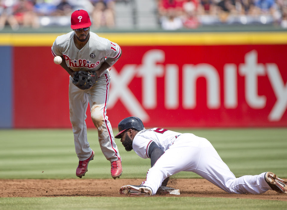 Photo - Atlanta Braves' Jason Heyward steals second base as Philadelphia Phillies shortstop Jimmy Rollins (11) handles the late throw in the first inning of a baseball game Monday, Sept. 1, 2014, in Atlanta. (AP Photo/John Bazemore)