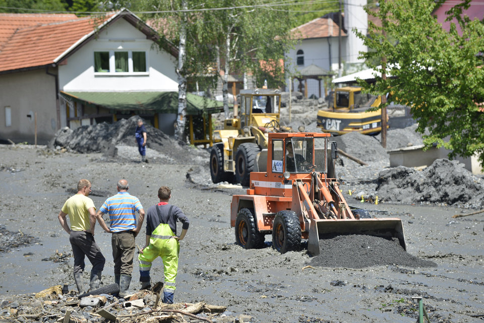 Photo - Heavy machinery is used to clean streets in the village of Topcic Polje, that was damaged in a landslide, near the Bosnian town of Zenica, 90 kilometers north of Sarajevo, on Monday May 19, 2014. At least 35 people have died in Serbia and Bosnia in the five days of flooding caused by unprecedented torrential rain, laying waste to entire towns and villages and sending tens of thousands of people out of their homes, authorities said. (AP Photo/Sulejman Omerbasic)