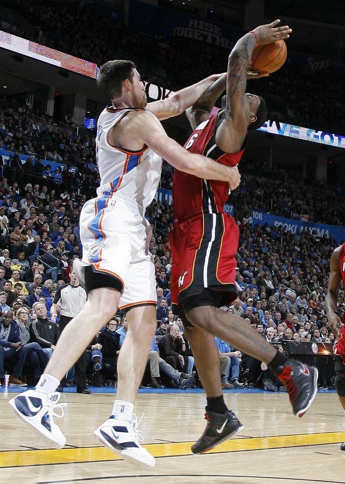 Photo - Oklahoma City's Nick Collison (4) defends Miami's LeBron James (6) as he shoots during the NBA basketball game between Oklahoma City and Miami at the OKC Arena in Oklahoma City, Thursday, Jan. 30, 2011. Photo by Sarah Phipps, The Oklahoman