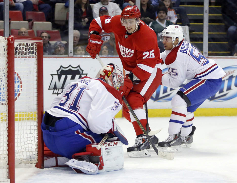 Photo - Detroit Red Wings' Tomas Jurco (26), of Slovakia, has his shot stopped by Montreal Canadiens goalie Carey Price (31) as teammate Francis Bouillon (55) helps defend the goal during the first period of an NHL hockey game Thursday, March 27, 2014, in Detroit. (AP Photo/Duane Burleson)