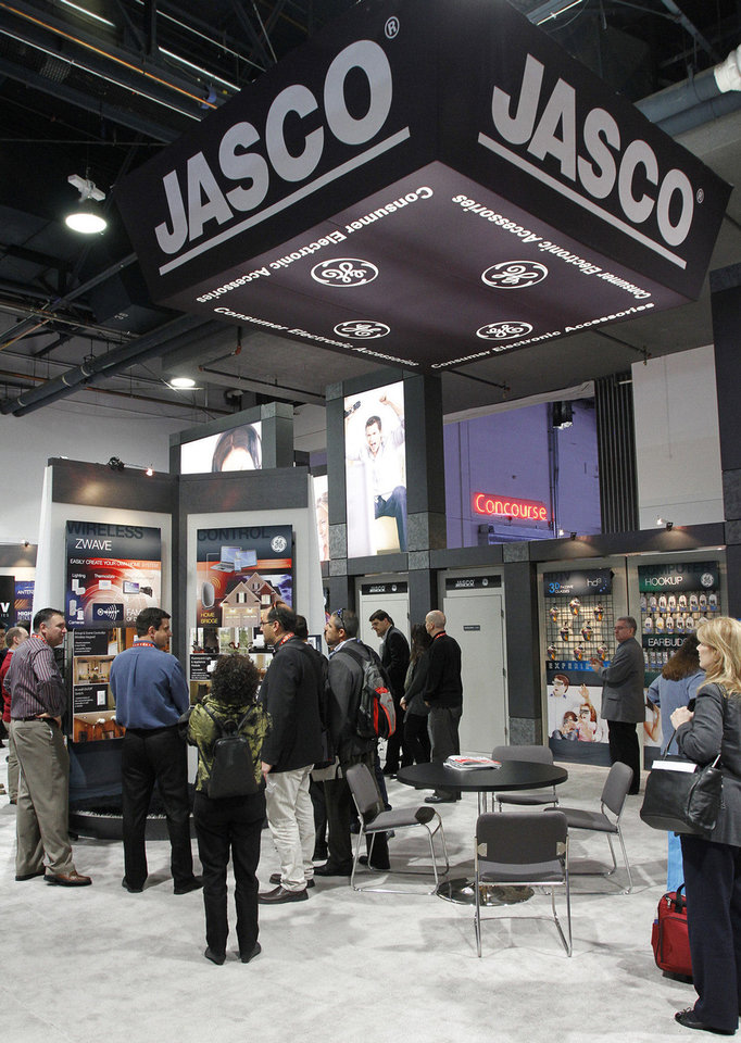 Photo - Attendees of the 2013 International Consumer Electronics Show look at products offered by Oklahoma City-based Jasco Products on Tuesday in Las Vegas.    - PAUL RIEDL