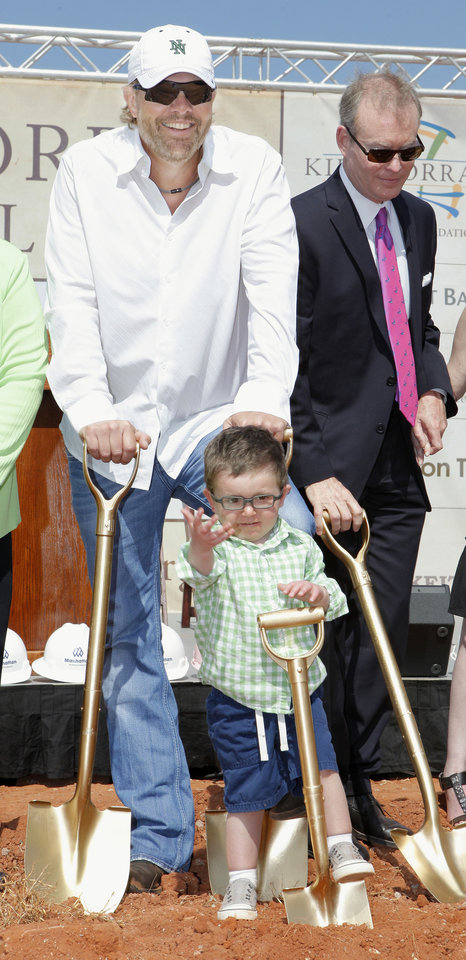 Photo - Toby Keith, left, Brock Hart, 3, and Oklahoma City Mayor Mick Cornett participate in groundbreaking for the OK Kids Korral, to be built  at NE 8 and Laird. Photo by Paul B. Southerland, The Oklahoman
