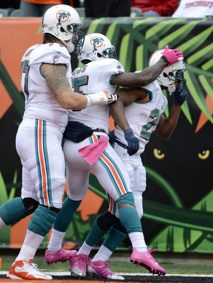 Photo -   Miami Dolphins running back Reggie Bush, right, is congratulated by tackle Jake Long, left, and wide receiver Davone Bess after scoring on a 13-yard run in the second half of an NFL football game against the Cincinnati Bengals, Sunday, Oct. 7, 2012, in Cincinnati. (AP Photo/Michael Keating)