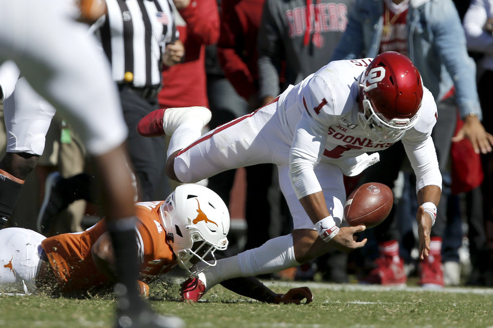 Photo - Oklahoma quarterback Jalen Hurts (1) fumbles the ball in front of Texas defensive back Anthony Cook (4) during the Red River Showdown college football game between the University of Oklahoma Sooners (OU) and the Texas Longhorns (UT) at Cotton Bowl Stadium in Dallas, Saturday, Oct. 12, 2019. [Bryan Terry/The Oklahoman]