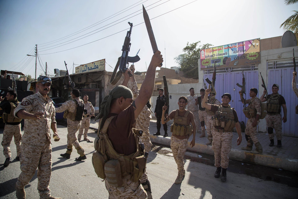 Photo - Iraqi security forces celebrate after clashes with followers of Shiite cleric Mahmoud al-Sarkhi, in front of his home in the Shiite holy city of Karbala, 50 miles (80 kilometers) south of Baghdad, Iraq, Wednesday, July 2, 2014. (AP Photo/Ahmed al-Husseini)