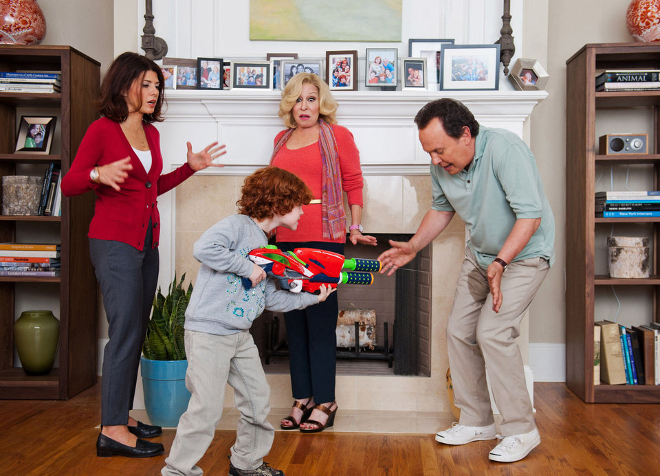 "Billy Crystal, right, as Artie reacts to his grandson, Kyle Harrison Breitkopf, center, Barker's water-rifle shenanigans while Marisa Tomei, left, as the mother Alice and Bette Midler as the grandmother, Diane, look on in a scene from the film, ""Parental Guidance.""  TWENTIETH CENTURY FOX PHOTO <strong>Phil Caruso</strong>"