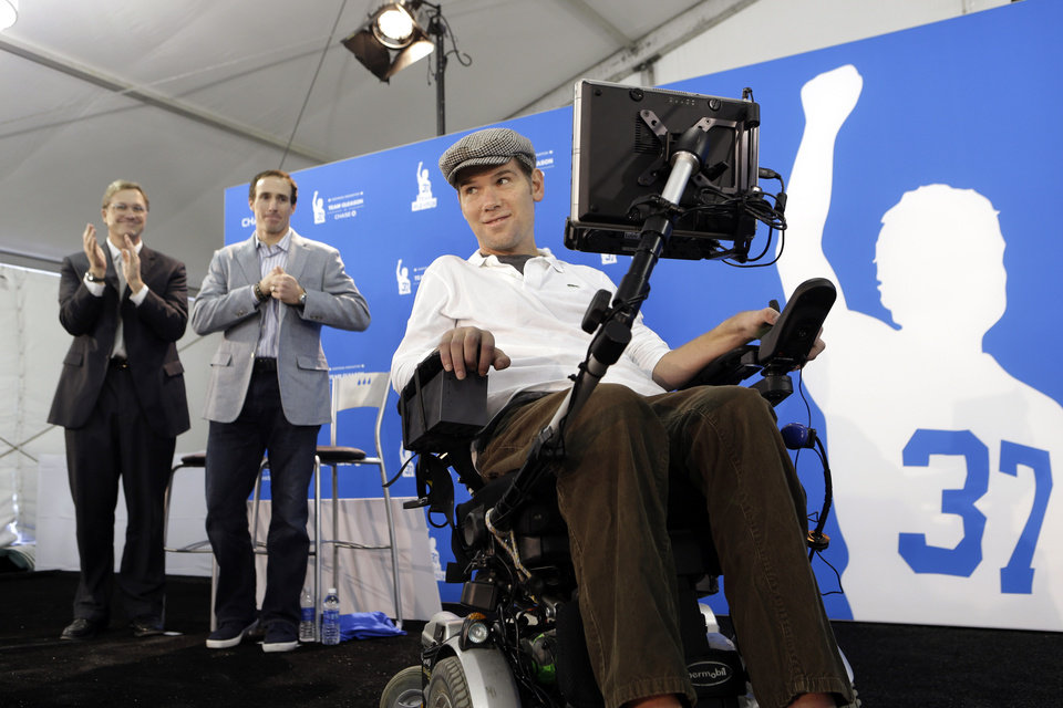 Steve Gleason, right, a former New Orleans Saints NFL football special teams standout who was diagnosed with amyotrophic lateral sclerosis, demonstrates the newest technology for Team Gleason House, a residence he is creating for up to 18 people with ALS and multiple sclerosis, during a news conference, Thursday, Jan. 17, 2013, in New Orleans. Work is still being done at the residence, which will make up the first floor of a 116-bed skilled nursing facility being developed by the St. Margaret\'s Daughters order in a mid-city hospital abandoned after the floods of Hurricane Katrina. Behind him is Saints quarterback Drew Brees, second from left, and Todd Maclin, of Chase Bank, which gave $350,000 to install the system made by Promixis LLC of Jupiter, Fla. (AP Photo/Gerald Herbert)